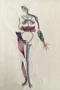 An outline of a naked woman is embroidered on linen in the same bone white colour as the linen. She stands legs together, her right hand covering her groin, her left hand, palm up, extended slightly to her side. She looks to the right. Her body is covered in squiggles, dots, and lines in blues, burgundies, greens and greys. Some of the markings are done in thick stitches, some in thin lines. Her belly is clear of markings. Her face is a mask of green lines, feathery lines cover her shoulders and chest. There is a thick band of intricate burgundy stitching around her waist. Her forearms and hands are covered in thick undulant lines. Her right leg has bands of burgundy along the muscles, with small dots around them. Her inner left leg has a thick line of blue running up it, with thin branches spreading towards her outer leg.