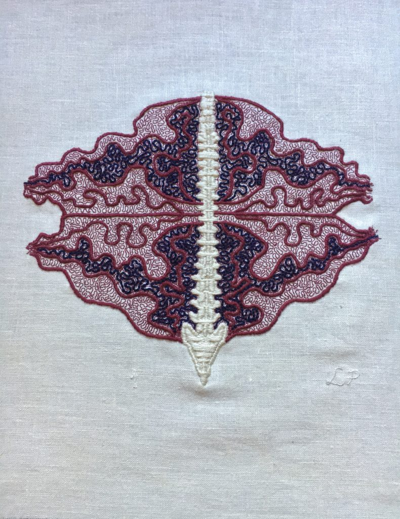 In the centre of some bone white linen, there is a spine embroidered in a thick satin stitch. Emanating from the spine are thick burgundy lines in an undulant oval shape. This oval is bisected across the middle. In the top half, there is a section outlined in burgundy filled with coiling blue lines and a similar section in the bottom half. The rest of the undulant oval is filled with fine coiling burgundy lines. The spine is very straight, the rest of the embroidery is very coiled and busy.